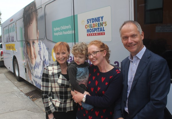 CEO Steffen Faurby stands with representatives from the Sydney Children's Hospital, in front of a bus decorated with images of a child and the Sydney' Children's Hospital's gold appeal marketing.