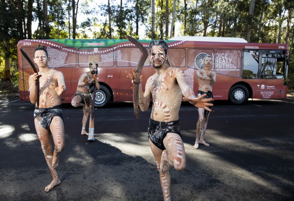 Indigenous dancers with traditional body paint perform in front of the NAIDOC bus, itself decorated with Indigenous artwork.