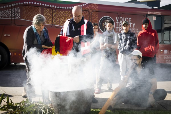 State Transit Employees bathe the Aboriginal Flag in smoke during an Aboriginal Smoking Ceremony to launch the 2019 NAIDOC bus.