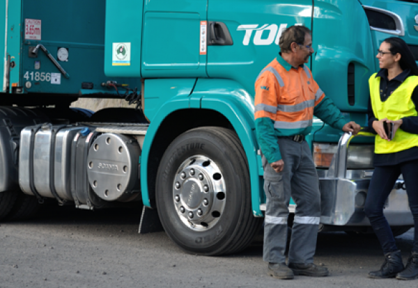Freight operators - two workers leaning against a truck