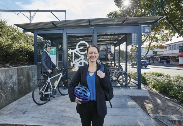 Photo of a woman standing in front of bike sheds and a train station