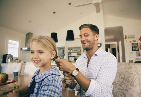 Photo of a man doing his daughter's hair before school